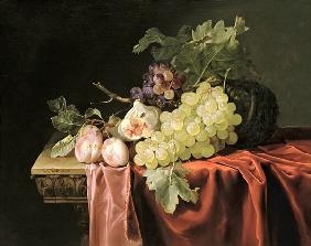 A still life with grapes, plums, figs and a melon on a partly draped stone ledge